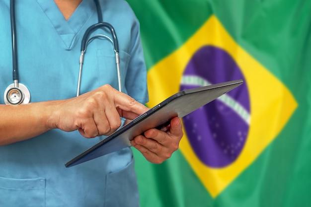 Cirurgião ou médico usando tablet digital no fundo da bandeira do brasil