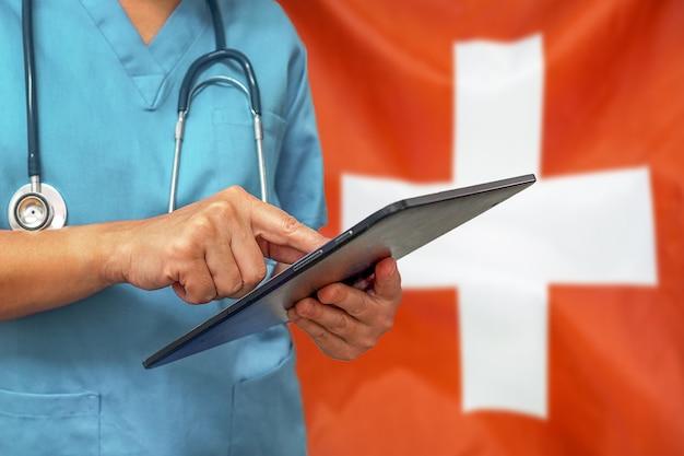 Cirurgião ou médico usando um tablet digital no fundo da bandeira da suíça