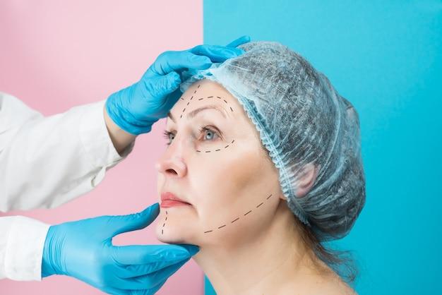Cirurgião plástico com luvas médicas está examinando o rosto de uma bela mulher de meia-idade, conceito de cirurgia plástica