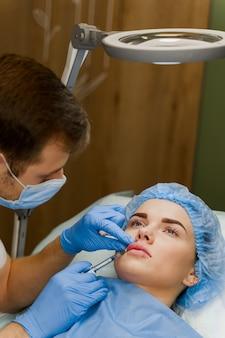 Cirurgião plástico faz injeção no lábio em clínica médica