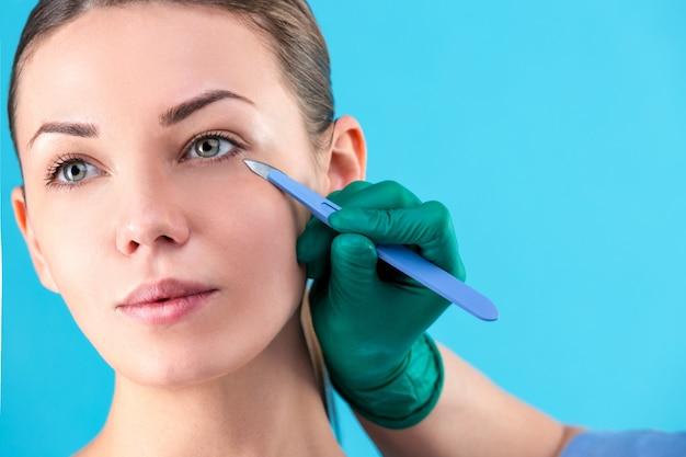 Cirurgião plástico que examina o cliente fêmea no escritório. médico, verificando o rosto da mulher, a pálpebra antes da cirurgia plástica, blefaroplastia. cirurgião ou esteticista mãos tocando o rosto de mulher