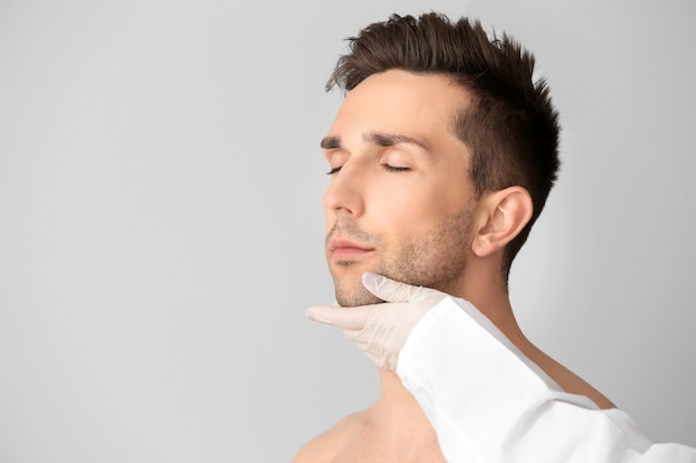 Cirurgião plástico tocando o rosto de um jovem em um fundo claro