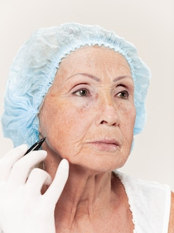 Cirurgião que faz a verificação da pele na mulher de meia idade antes da cirurgia plástica