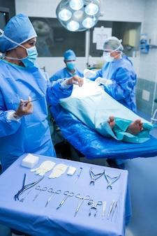 Cirurgião que olham tesoura no quarto de operação