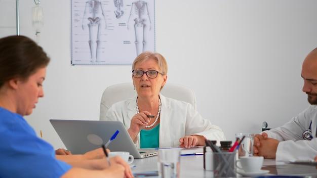 Cirurgião sênior, explicando o tratamento aos colegas de trabalho, apresentando o plano durante a conferência médica, sentado na mesa de reunião na clínica moderna. equipe profissional tomando notas enquanto o médico especialista discute.