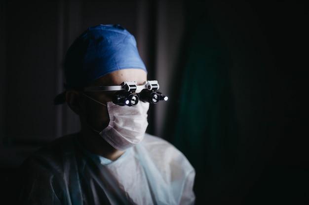 Cirurgião usando lupas binoculares opera em um paciente em uma sala de cirurgia escura