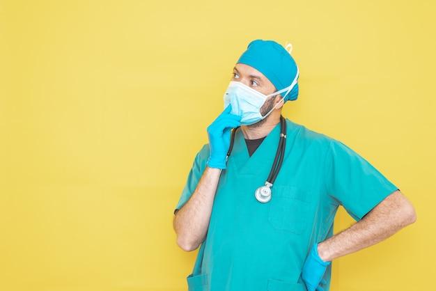 Cirurgião vestido com uniforme de sala de cirurgia e estetoscópio, sobre fundo amarelo.