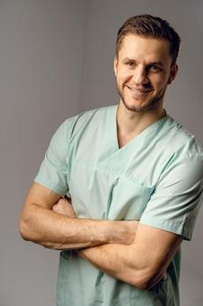 Cirurgião vestindo túnica médica, sorrindo e posando. belo médico feliz posando