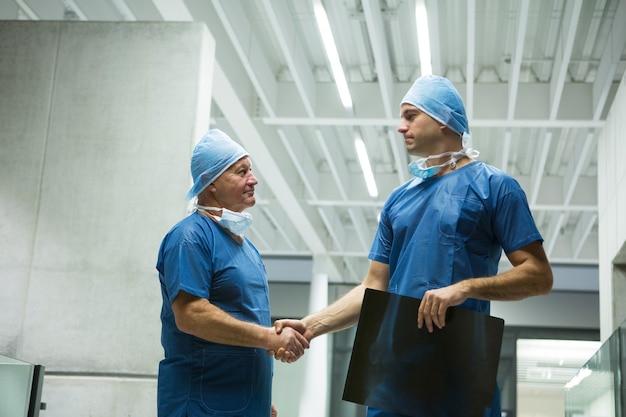 Cirurgiões do sexo masculino segurando um raio-x enquanto apertam as mãos