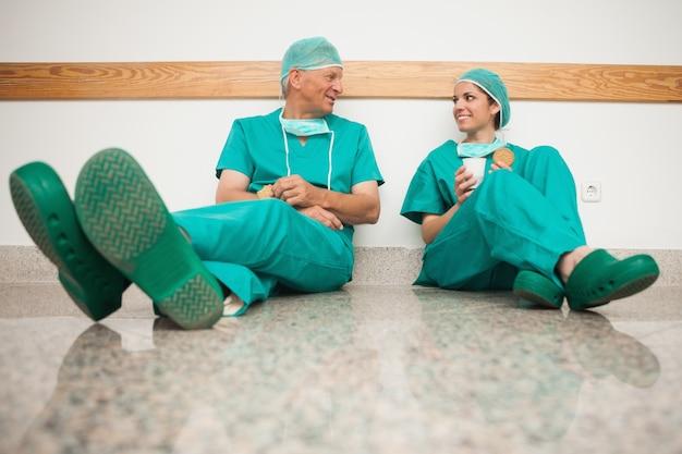Cirurgiões falando enquanto estão sentados no chão