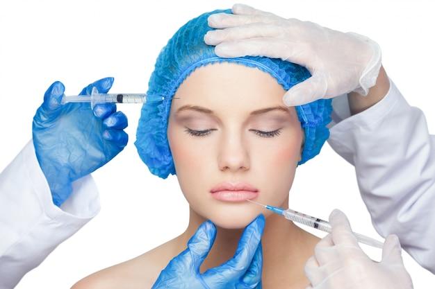 Cirurgiões fazendo injeção na loira calma