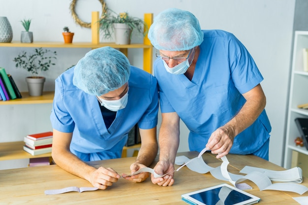 Cirurgiões lendo os resultados dos testes
