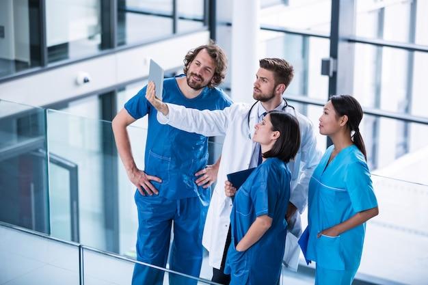 Cirurgiões, médico e enfermeira olhando tablet digital