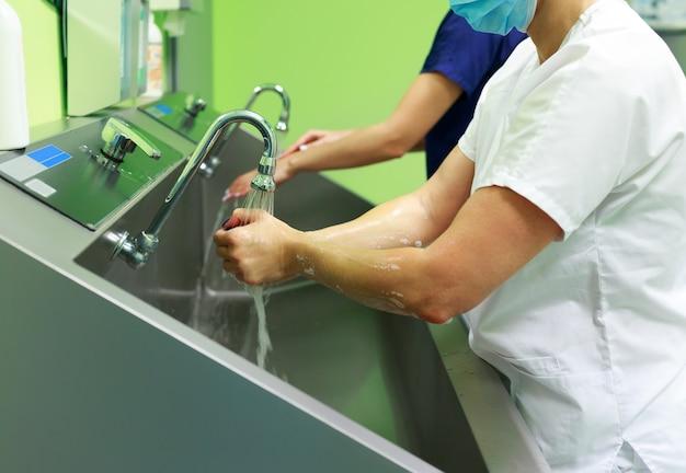 Cirurgiões no hospital lavando as mãos