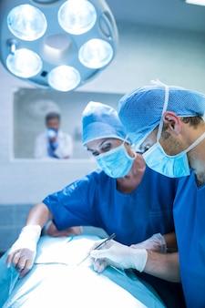 Cirurgiões que executam a operação no quarto de operação