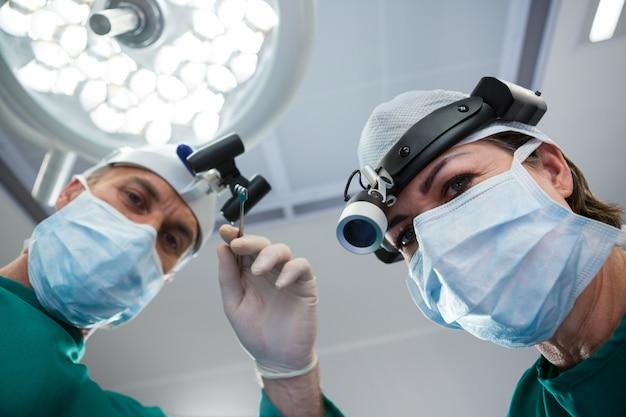 Cirurgiões segurando o instrumento cirúrgico