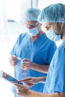 Cirurgiões usando tablet e lendo os resultados dos testes