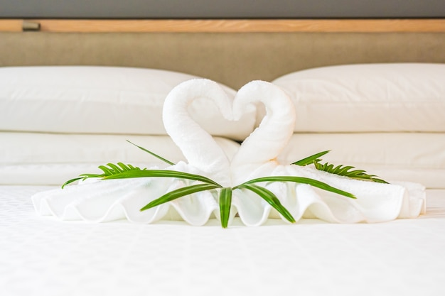 Cisne de toalha branca na decoração da cama no interior do quarto