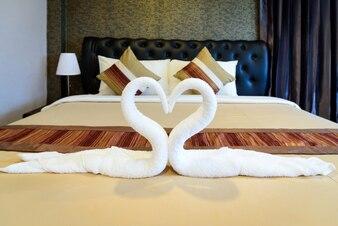 Cisnes de toalha dadas forma ou toalha que dão forma à forma do coração na cama luxuosa na sala de hotel.