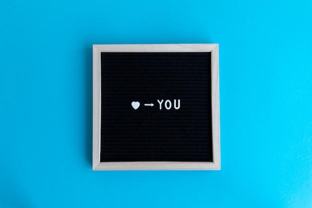 Citação de amo você em uma placa emoldurada de madeira sobre um fundo colorido