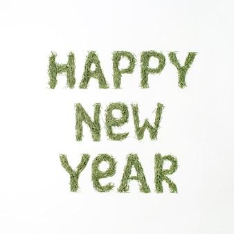 Cite o feliz ano novo feito de agulhas de abeto isoladas na superfície branca. camada plana, vista superior