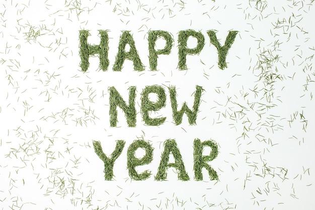 Cite o feliz ano novo feito de agulhas de coníferas na superfície branca. camada plana, vista superior