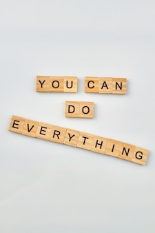 Cite por acreditar em si mesmo. conceito de autoconfiança feito de blocos de letras de madeira em fundo branco.