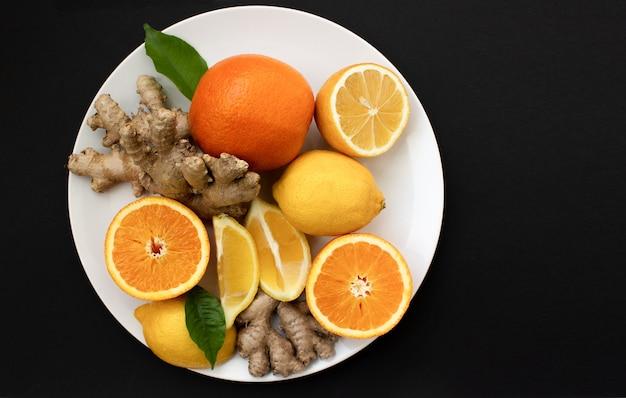 Cítricos em um prato branco laranjas, limões e gengibre em um prato branco em um fundo pretovista superior