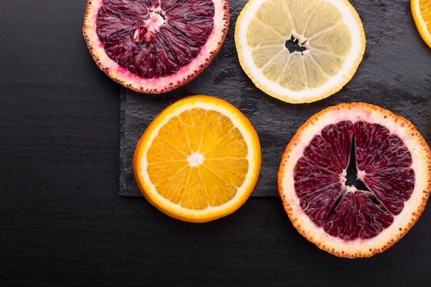 Cítricos frescos maduros. limões, laranjas vermelhas e laranjas na mesa de pedra escura. copie o espaço
