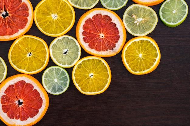Citrinos cortados ao meio - laranjas, limões, limão, tangerinas, toranja em um fundo de madeira