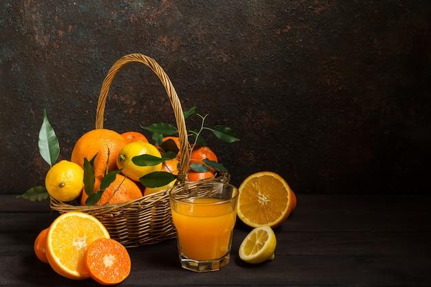 Citrinos de limão laranja em uma cesta e suco em um fundo escuro, dieta alimentar saudável