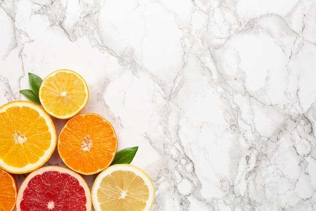 Citrinos na superfície de mármore com copyspace, frutas flatlay, composição mínima de verão com toranja, limão, tangerina e laranja