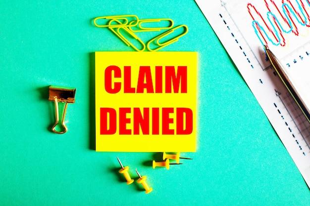 Claim denied está escrito em vermelho em um adesivo amarelo em um fundo verde perto do gráfico e do lápis