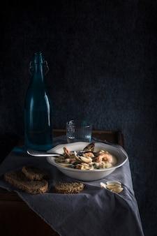 Clam chowder em um prato branco. os principais ingredientes são mariscos, caldo, manteiga, batata e cebola.
