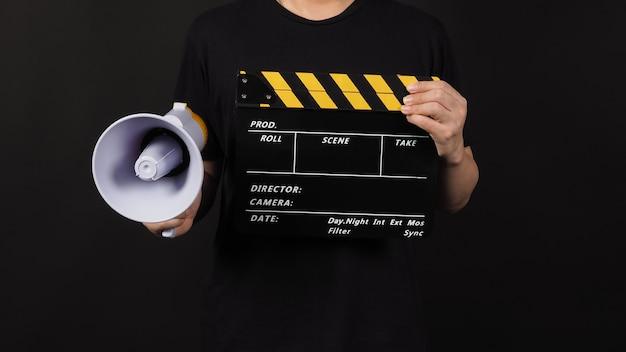 Clapper board ou filme ardósia preto e amarelo e megafone na mão do homem isolado no fundo preto.