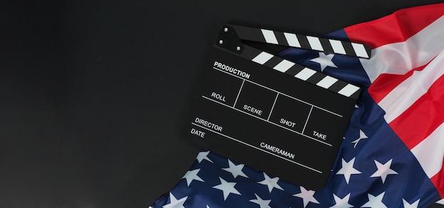 Clapper board ou lousa de filme e bandeira dos estados unidos da américa (eua) em fundo preto.