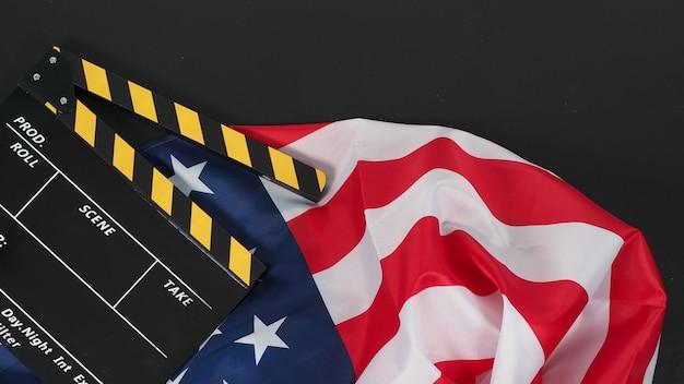Clapper board preto e amarelo ou ardósia do filme e a bandeira dos estados unidos da américa (eua) em fundo preto.
