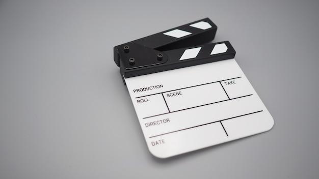 Clapperboard branco ou uso de ardósia de filme na produção de vídeo, cinema, indústria do cinema em fundo cinza.