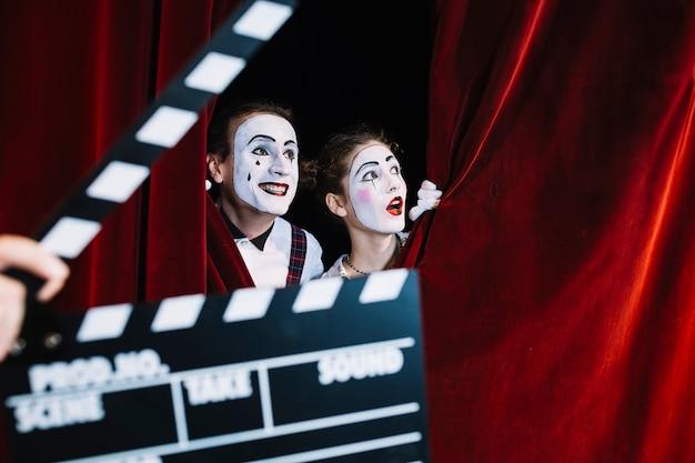Clapperboard na frente do casal animado mime a espreitar por trás da cortina vermelha