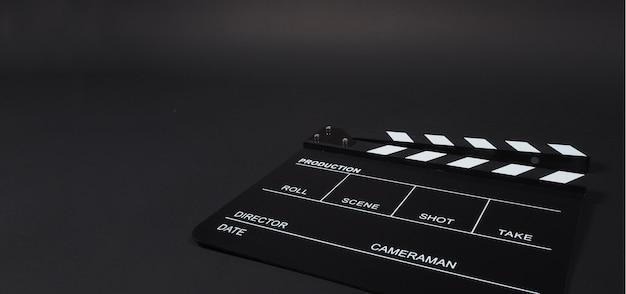 Clapperboard ou clap board ou movie slate uso na produção de vídeo, cinema, indústria do cinema em fundo preto.
