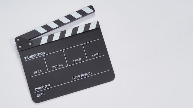 Clapperboard ou movie slate uso na produção de vídeo, cinema e indústria cinematográfica. é de cor preta sobre fundo de papel branco.