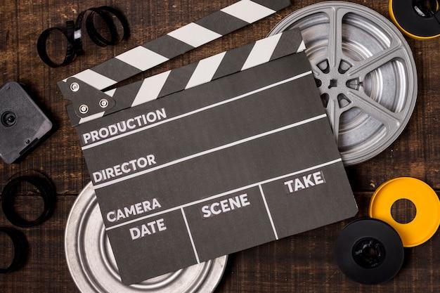 Clapperboard sobre o rolo de filme e negativos em pano de fundo de madeira