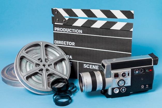 Claquete; bobina de filme e filmadora em fundo azul