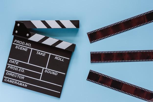 Claquete de cinema com filme sobre fundo azul para equipamentos de filmagem