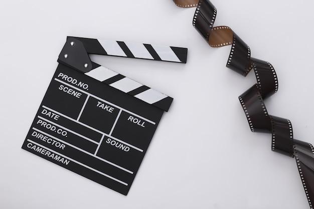 Claquete de cinema com fita de filme em fundo branco. cinema, produção de cinema, indústria do entretenimento. vista do topo