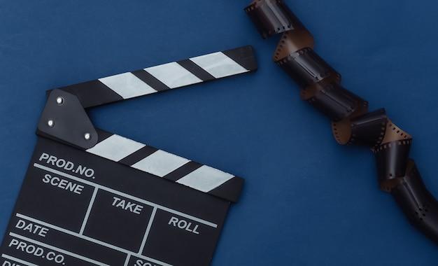 Claquete de cinema com fita de filme no fundo azul clássico. cinema, produção de cinema, indústria do entretenimento. cor 2020. vista superior