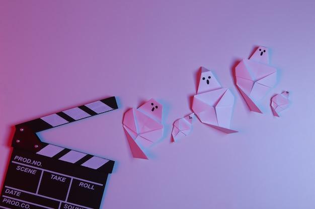 Claquete de cinema e fantasmas de origami em luz gradiente de néon vermelho-azul. filme assustador de halloween