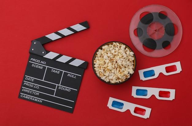 Claquete de cinema, tigela de pipoca, óculos 3d, rolo de filme em fundo vermelho. indústria do entretenimento. vista do topo. postura plana
