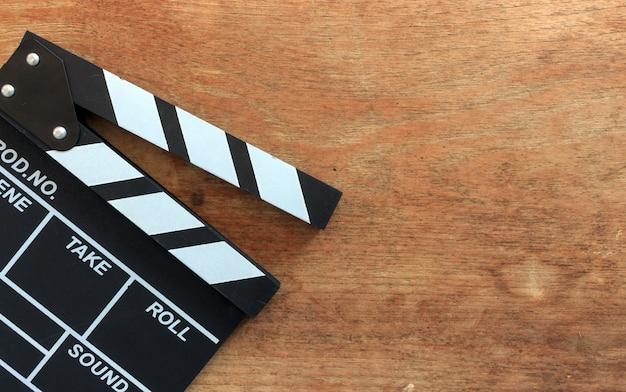 Claquete de filme closeup na mesa de madeira com foco suave e sobre a luz no fundo