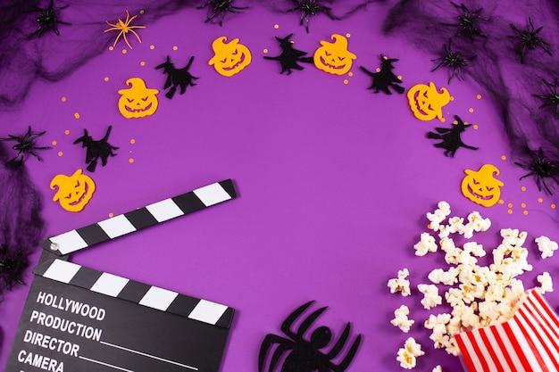 Claquete de filme em teias de aranha olhos fantasmas de aranhas em fundo lilás roxo